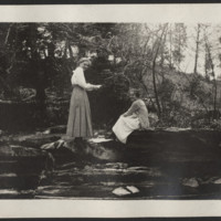 Students sitting by a river
