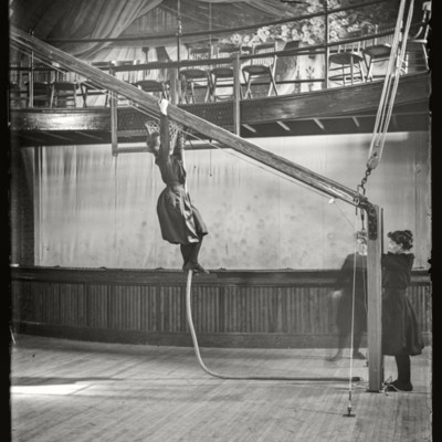 Physical Ed: gym classes, Miss Wardwell on ladder, Gymnasium interior (1900-1903)